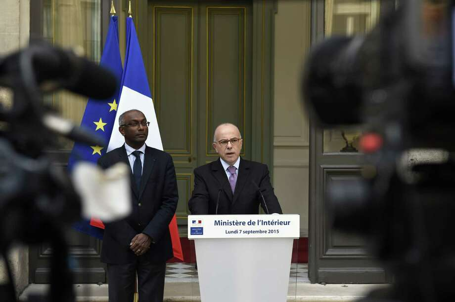 French Interior minister Bernard Cazeneuve (C) delivers a speech on measures France has decided to take to welcome more asylum-seekers, on September 7, 2015 at the Interior ministry in Paris. As European leaders stepped up efforts to tackle the historic migrants crisis, France said it would take 24,000 more asylum-seekers under a European plan to relocate 120,000 refugees from hard-hit frontline countries. AFP PHOTO / LOIC VENANCELOIC VENANCE/AFP/Getty Images ORG XMIT: 5 Photo: LOIC VENANCE / LOIC VENANCE