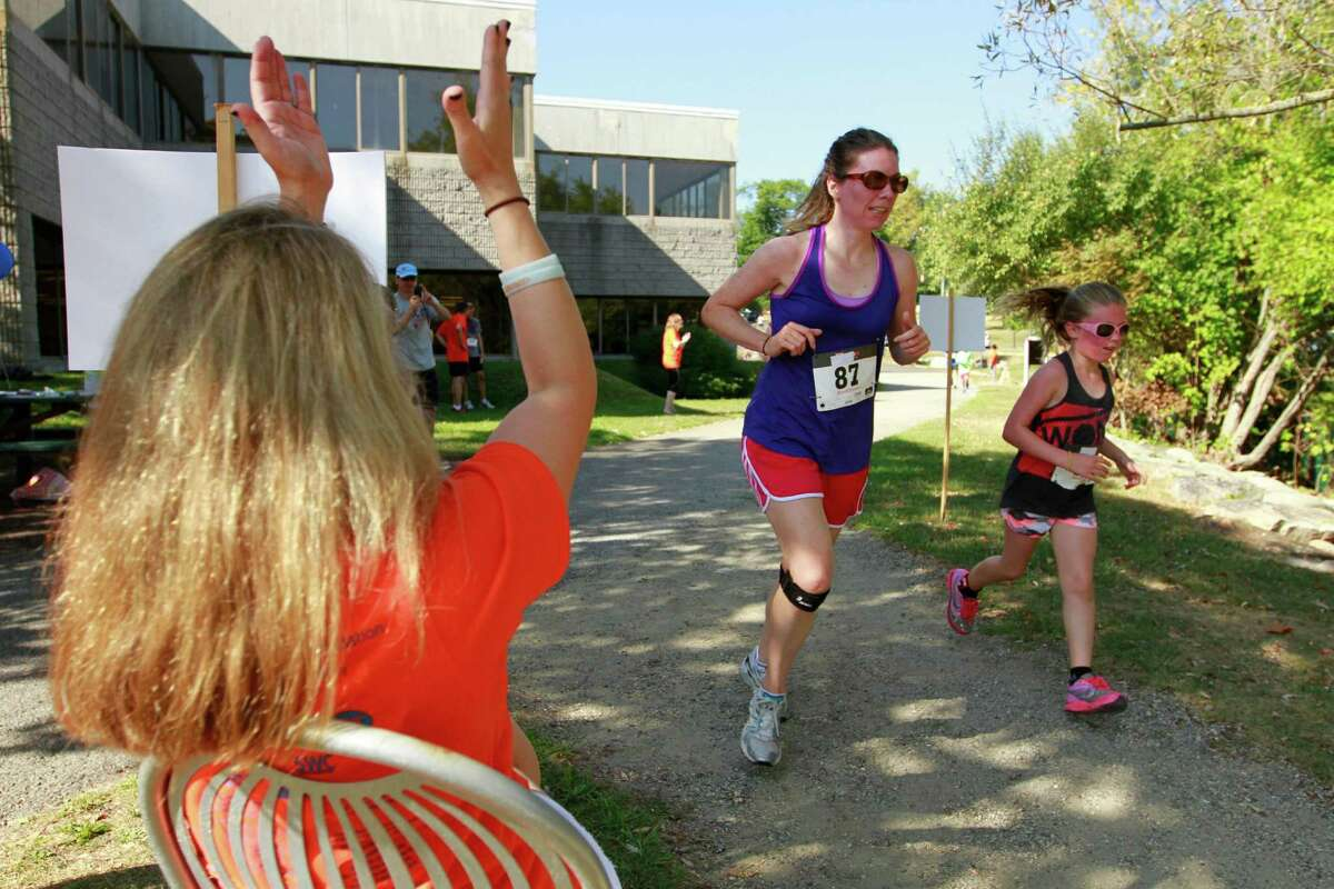 Esther Parker, center, and her daughter Madison pass the cheers of voluteers during the annual Give a Child a Jump Start - 5k/10k Walk/Run &Family Fun Day at the JCC of Stamford on Monday Sept. 7, 2015. The event drew more than 400 participants and raise over $40,000 to help support the JCC Jump Start and Early Childhood Special Needs programs.
