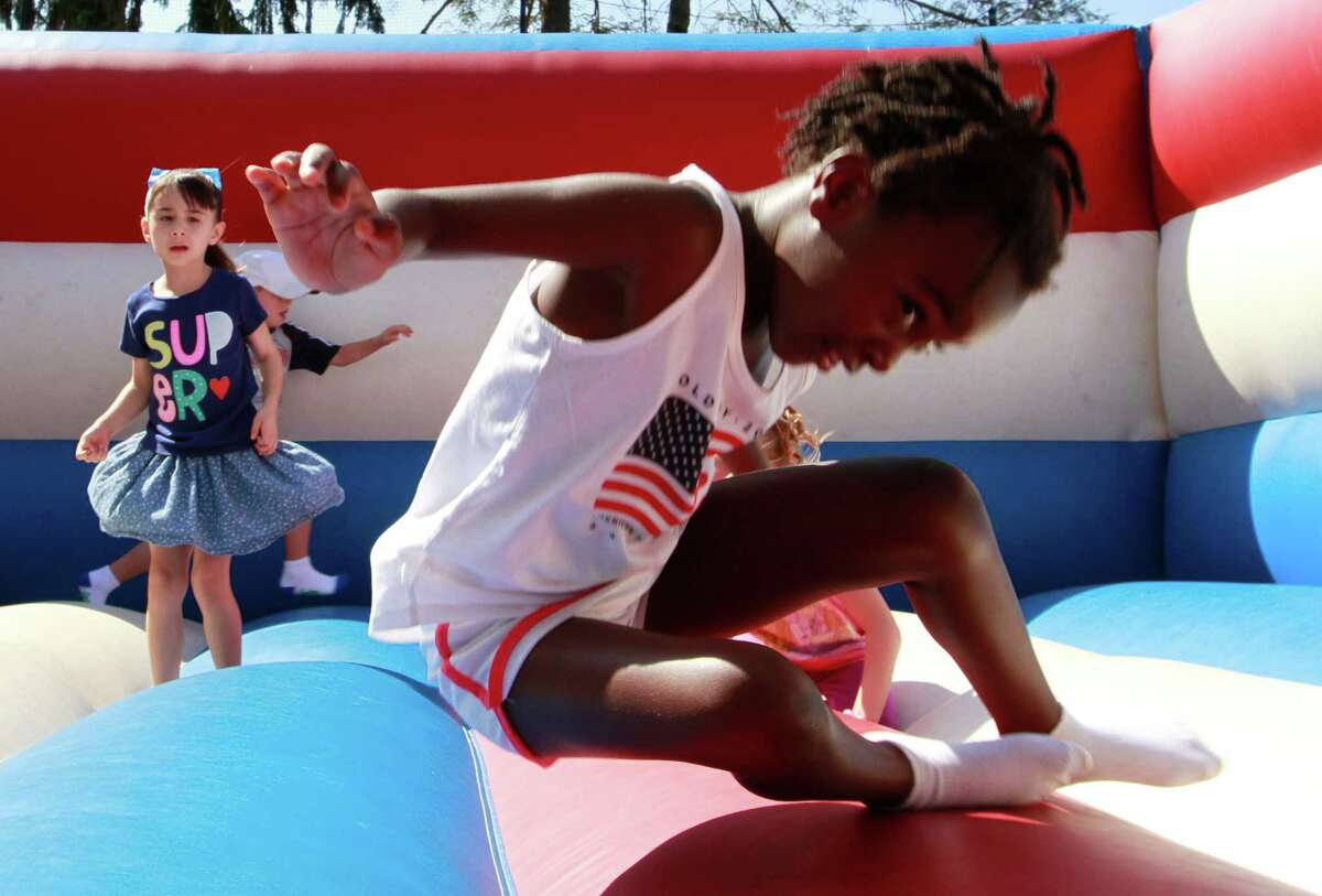 Yeabsera Williams, 7 of Trumbull plays with other children in a Bouncy House during the annual Give a Child a Jump Start - 5k/10k Walk/Run &Family Fun Day at the JCC of Stamford on Monday Sept. 7, 2015. The event drew more than 400 participants and raise over $40,000 to help support the JCC Jump Start and Early Childhood Special Needs programs.