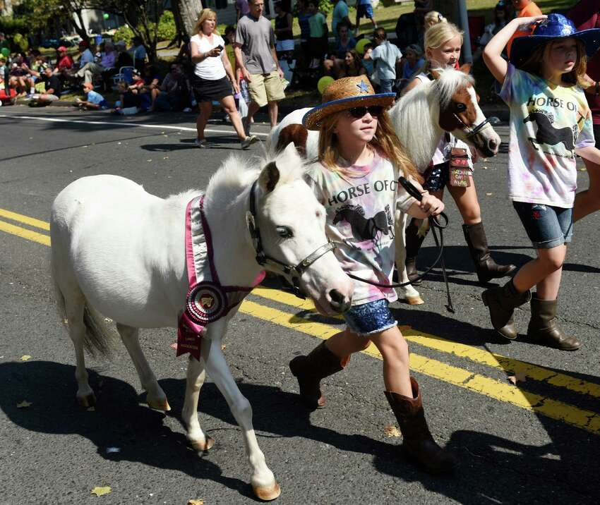 Riley Roksvold, 9, of Brookfield, marches beside her pony with the 4H Club's Happy Hoofers during the 54th Annual Newtown Labor Day Parade in Newtown, Conn. Monday, Sept. 7, 2015. The theme for 2015 was