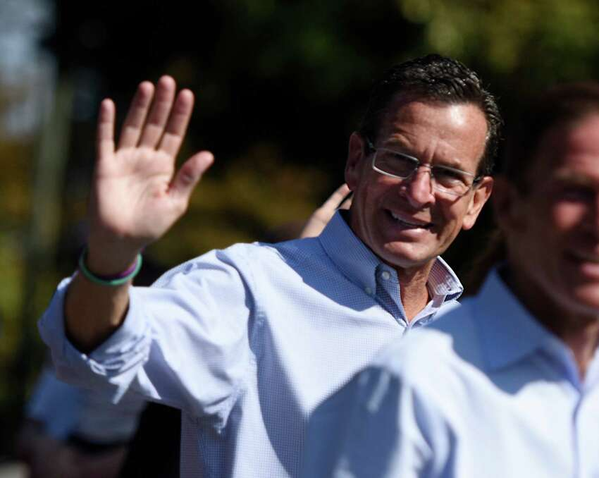 Connecticut Gov. Dannel P. Malloy waves to the crowd while marching in the 54th Annual Newtown Labor Day Parade in Newtown, Conn. Monday, Sept. 7, 2015. The theme for 2015 was