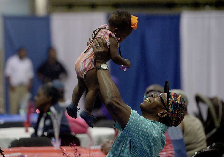 James Freeman plays with a cousin's daughter, 11-month-old Shaunetzy Green, as he and family enjoy the annual Labor Day Picnic hosted for the community by the Solid Rock Community Church Monday at the Beaumont Civic Center. Attendees filled the room, lining up for a meal, games and children's play zone and entertainment. The event opened with several speeches by community leaders and politicians, reflecting on the spirit of the holiday. Photo taken Monday, September 7, 2015 Photo by Kim Brent / Beaumont Enterprise