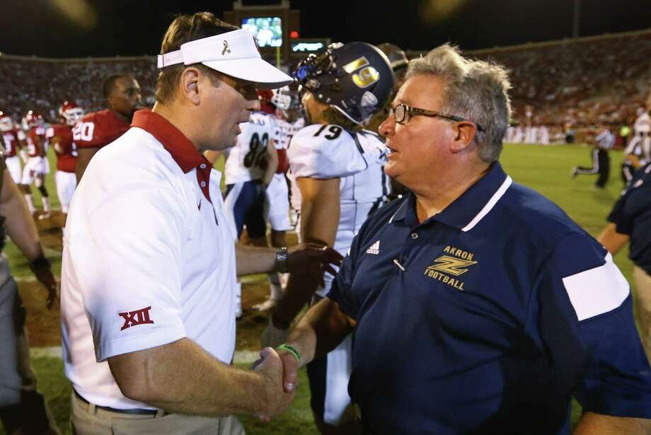 Oklahoma head coach Bob Stoops, left, shakes hands with Akron head coach Terry Bowden, right, following their game in Norman, Okla., on Sept. 5, 2015. Oklahoma won 41-3. Photo: Sue Ogrocki /Associated Press / AP