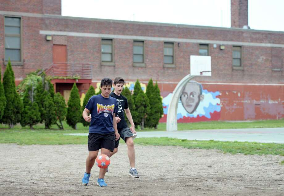 Thirteen-year-old Bernard Schuler controls the ball during a neighborhood game of soccer Thursday, June 4, 2015, outside the  now defunct Boys and Girls Club in the North End of Bridgeport. Photo: Autumn Driscoll / Autumn Driscoll / Connecticut Post