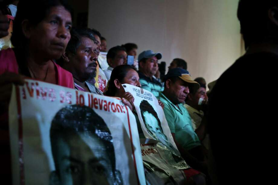 Parents of the 43 teachers' college students hold up images of their missing sons as they listen in to a conference in Mexico City, Sunday, Sept. 5, 2015. An independent report presented Sunday dismantled the Mexican government's investigation into last year's disappearance of the 43 students, saying the prosecutor's contention that they were incinerated in a giant pyre never happened and fueling the anger of parents who still don't know what happened to their sons. (AP Photo/Emilio Espejel) Photo: Emilio Espejel, STR / AP