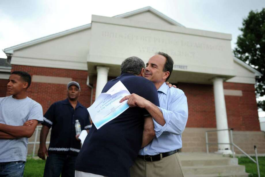 Mayoral candidate Joe Ganim gets a hug from supporter Rich Carraro, President of the West End Business Association, outside of the former Bridgeport Police Department West Precinct on State Street Wednesday, July 15, 2015. Photo: Autumn Driscoll / Hearst Connecticut Media / Connecticut Post