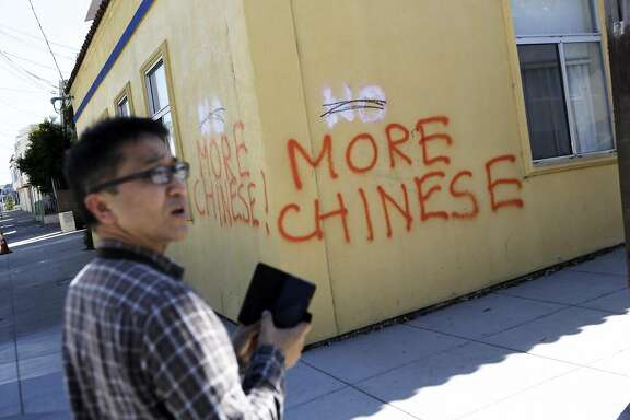 Eric Li of San Francisco stops on his walk home to take a photo of anti Chinese graffiti at the corner of Somerset St. and Silver Ave in San Francisco, Ca. on Monday, September 7, 2015.
