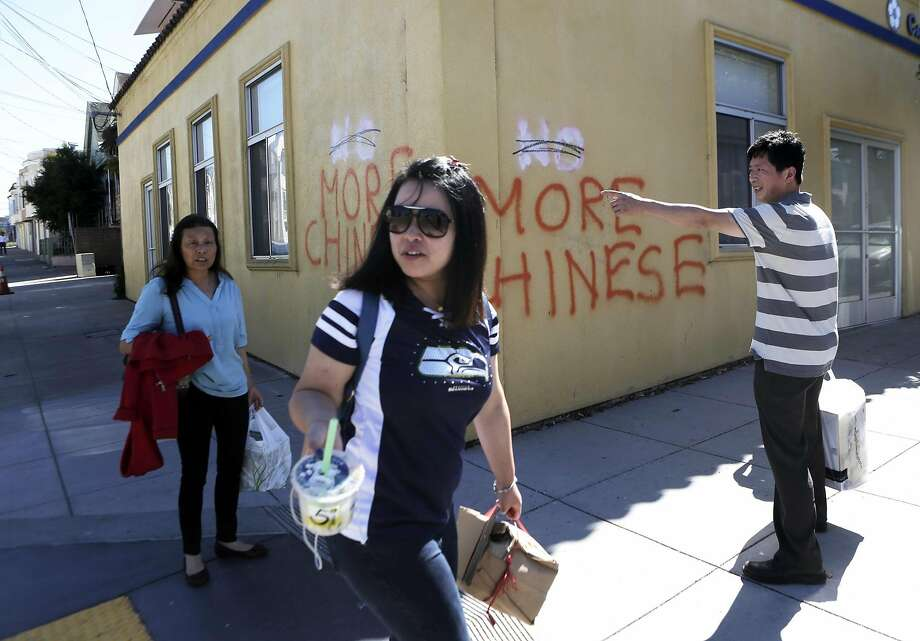 A group of people walk by anti Chinese graffiti at the corner of Somerset St. and Silver Ave in San Francisco, Ca. on Monday, September 7, 2015. Photo: Dorothy Edwards, The Chronicle
