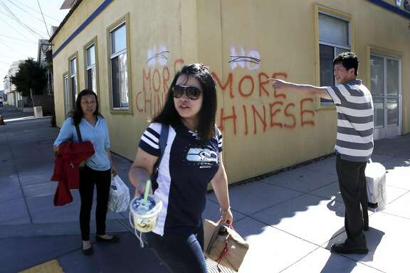 A group of people walk by anti Chinese graffiti at the corner of Somerset St. and Silver Ave in San Francisco, Ca. on Monday, September 7, 2015.