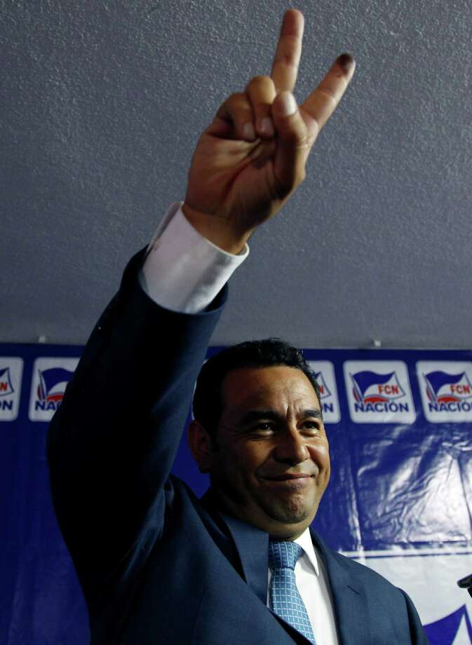 Television comedian and presidential candidate for the National Front of Convergence party Jimmy Morales, flashes the V sign for photographers during a press conference at his party headquarters in Guatemala City, Sunday, Sept. 6, 2015. Guatemalans headed to the polls Sunday to elect a president, vice president, members of Congress and the Central American Parliament, and local authorities for municipalities nationwide. (AP Photo/Luis Soto) Photo: Luis Soto, STR / AP