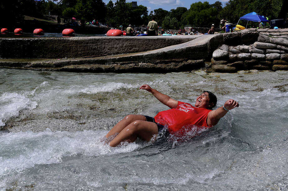 Jenny Padilla, of Houston, slides down a chute on the Comal River at Prince Solms Park in New Braunfels on Monday, Sept. 7, 2015. Photo: Lisa Krantz, Staff / SAN ANTONIO EXPRESS-NEWS / SAN ANTONIO EXPRESS-NEWS