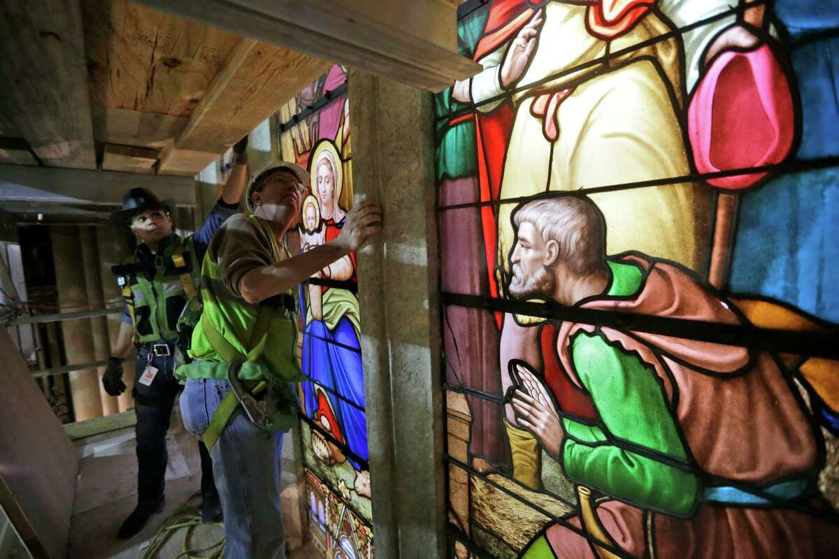 In this Wednesday, May 6, 2015 photo, stained glass foreman Jim Edbrooke, left, and foreman Anthony Del Orbe prepare to hoist a newly restored stained glass panel into place at St. Patrick's Cathedral in New York. A three-year restoration project at the cathedral is coming to an end, just in time for a late September visit from Pope Francis. (AP Photo/Mary Altaffer) ORG XMIT: NY827
