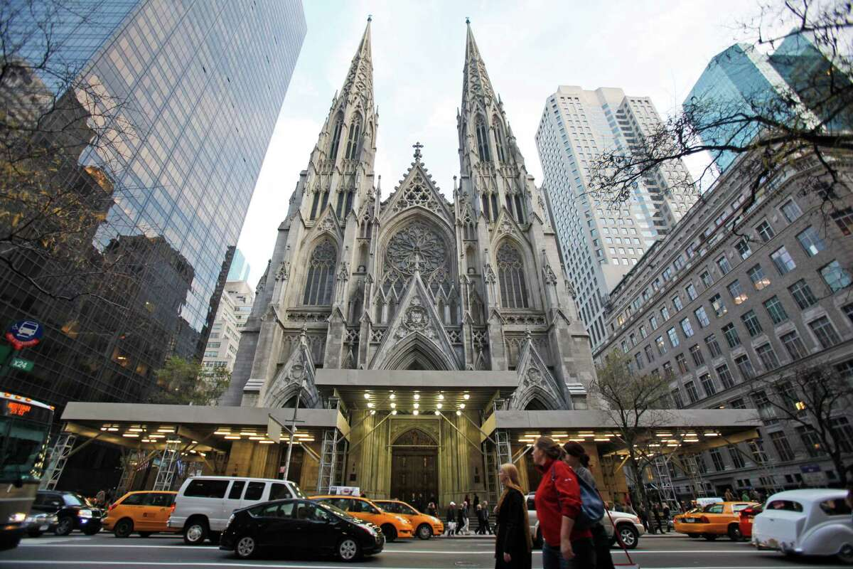 FILE - In this Nov. 20, 2010 photo, visitors to New York's Fifth Avenue walk past St. Patrick's Cathedral. The 2,200-seat white marble cathedral opened in 1879. In September 2015, the restoration project at the cathedral is coming to an end, in time for a visit from Pope Francis. (AP Photo/Mary Altaffer, File) ORG XMIT: NY811