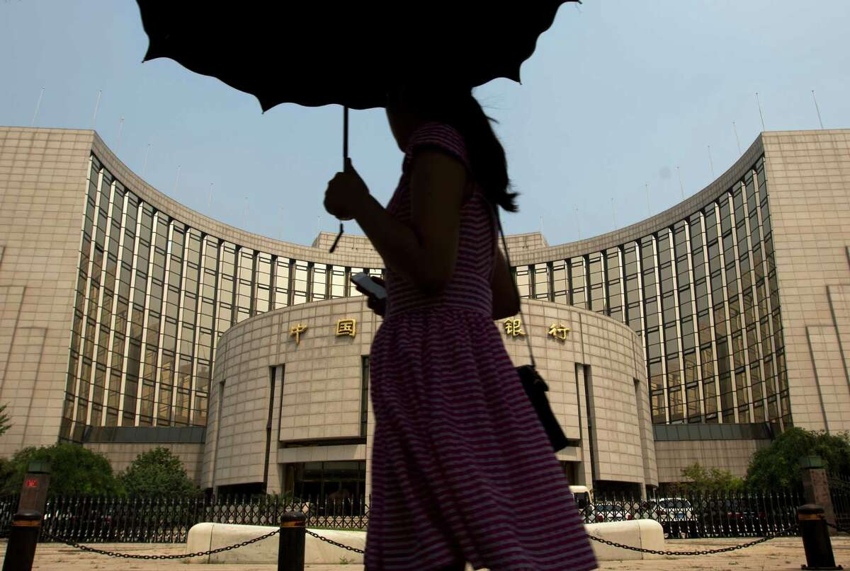 In this Aug. 11, 2015 photo, a woman holding an umbrella walks past China's central bank People's Bank of China in Beijing. China?'s central bank governor has told a meeting of the G-20 that China?'s currency has stabilized against the dollar after the country?'s surprise announcement last month to revalue the yuan amid stock market turmoil. (AP Photo/Andy Wong) ORG XMIT: XAW101