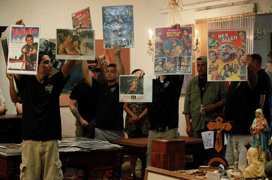 Vogt Auction staffers hold up old movie posters during the auction featuring items from the estate of movie theater impressario John Santikos. Items from other suppliers were also auctioned. Photo: John Davenport /San Antonio Express-News / ©San Antonio Express-News/John Davenport