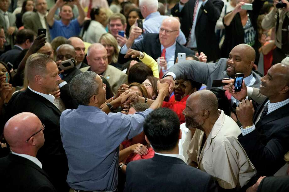 President Barack Obama greets members of the crowd after speaking at the Greater Boston Labor Council Labor Day Breakfast, Monday, Sept. 7, 2015, in Boson. Obama will sign an Executive Order requiring federal contractors to offer their employees up to seven days of paid sick leave per year. (AP Photo/Andrew Harnik) ORG XMIT: MAAH124 Photo: Andrew Harnik / AP