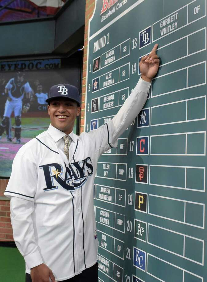 Outfielder Garrett Whitley from Niskayuna High School in Niskayuna, N.Y. points to his name on the board after being selected by the Tampa Bay Rays with the 13th selection at the 2015 MLB baseball draft Monday, June 8, 2015, in Secaucus, N.J.  (AP Photo/Bill Kostroun) ORG XMIT: NJBK109 Photo: Bill Kostroun / FR51951 AP