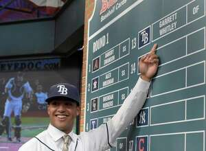 Outfielder Garrett Whitley from Niskayuna High School in Niskayuna, N.Y. points to his name on the board after being selected by the Tampa Bay Rays with the 13th selection at the 2015 MLB baseball draft Monday, June 8, 2015, in Secaucus, N.J.  (AP Photo/Bill Kostroun) ORG XMIT: NJBK109