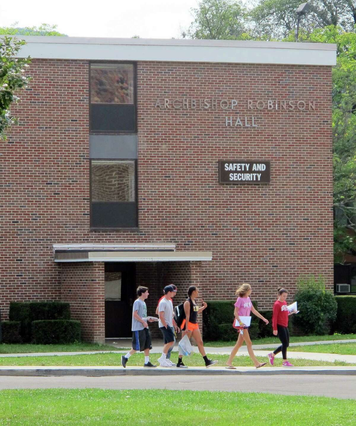 In this Aug. 29, 2015 photo, students walk past the public safety building at St. Bonaventure University in St. Bonaventure, N.Y. Students at New York state's private colleges and universities return to campus with a new, affirmative sexual consent policy to combat campus sexual violence. A bill signed by Gov. Andrew Cuomo over the summer expands on a policy in effect at public colleges which includes a