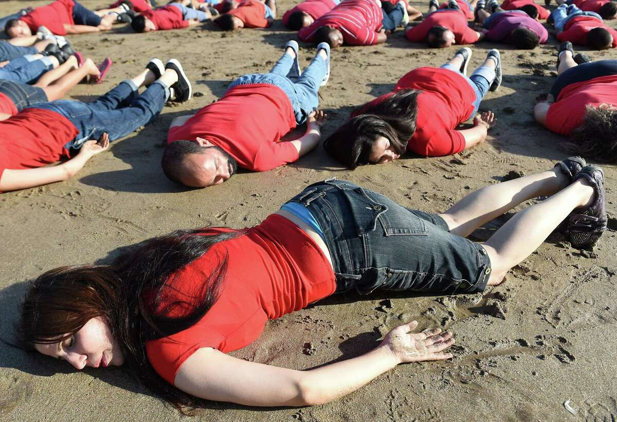 Moroccans adopt the position of the lifeless body of Syrian three-year-old Aylan Kurdi, who drowned while fleeing the Syrian war, during a rally to pay tribute to the tiny boy on September 7, 2015 on a beach in the capital Rabat. Aylan's body was photographed lying face down in the sand with red and blue clothing on a Turkish beach, in a bleak image that rapidly went viral on social media. AFP PHOTO / FADEL SENNAFADEL SENNA/AFP/Getty Images