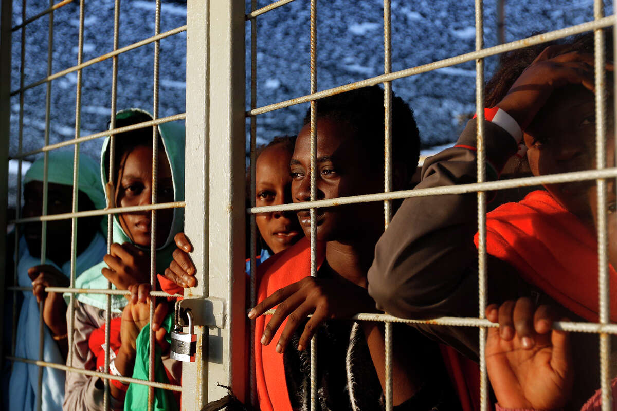 FILE - In this Thursday, Sept. 3, 2015 file photo, migrants rescued off the Libyan coast peer out a gate on the Siem Pilot Norwegian ship to get the first sight of the island of Sardinia as they sail in the Mediterranean sea towards the Italian port of Cagliari. As of September 2015, more than 2,800 migrants have died trying to reach Europe, mostly at sea, according to the International Organization for Migration. (AP Photo/Gregorio Borgia, File) ORG XMIT: NY841