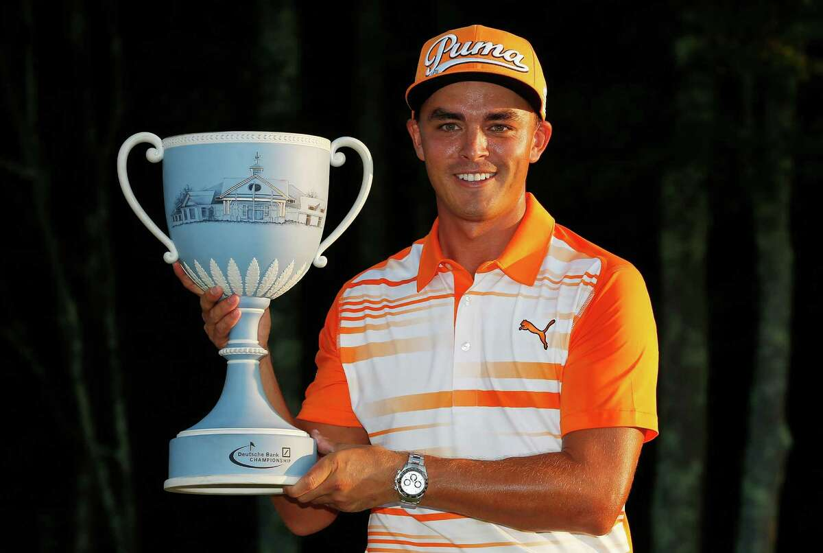 Rickie Fowler holds the trophy after winning the Deutsche Bank Championship golf tournament in Norton, Mass., Monday, Sept. 7, 2015. (AP Photo/Michael Dwyer) ORG XMIT: MAMD109