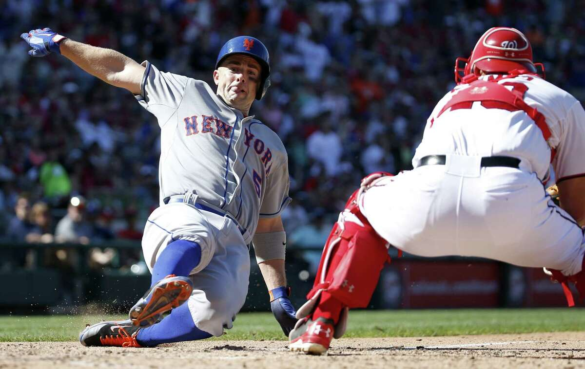 New York Mets' David Wright, left, scores as Washington Nationals catcher Wilson Ramos, right, cannot make the tag in time during the seventh inning of a baseball game at Nationals Park, Monday, Sept. 7, 2015, in Washington. Wright scored on a double by Yoenis Cespedes. The Mets won 8-5. (AP Photo/Alex Brandon) ORG XMIT: NAT119