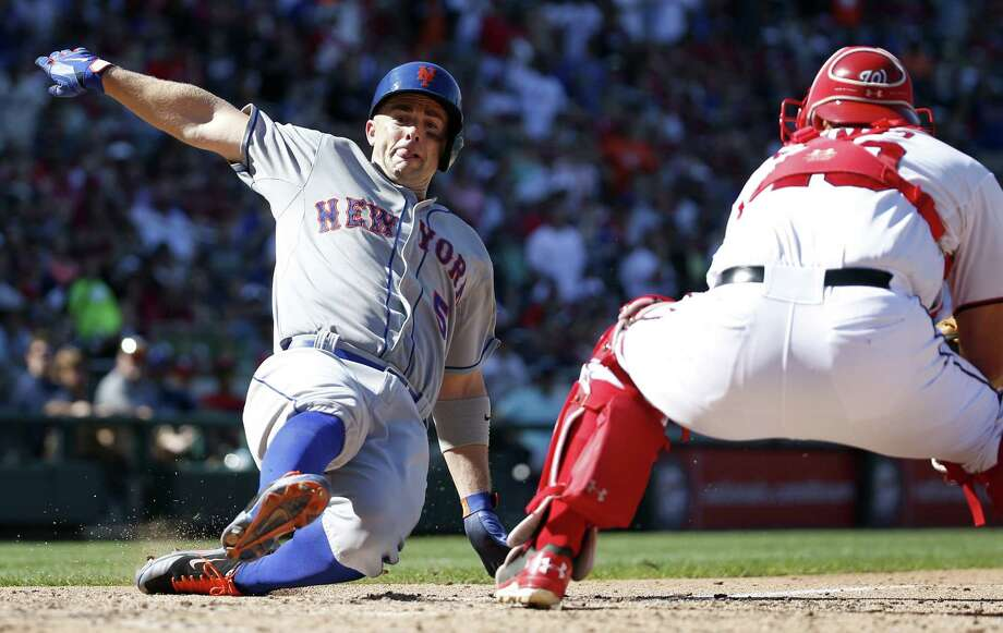 New York Mets' David Wright, left, scores as Washington Nationals catcher Wilson Ramos, right, cannot make the tag in time during the seventh inning of a baseball game at Nationals Park, Monday, Sept. 7, 2015, in Washington. Wright scored on a double by Yoenis Cespedes. The Mets won 8-5. (AP Photo/Alex Brandon) ORG XMIT: NAT119 Photo: Alex Brandon / AP