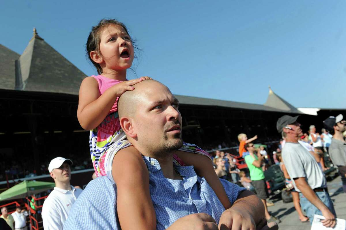 Natalie Dion, 4, of Mechanicville cheers for her horse from the shoulders of her father, Jeremy Dion, on final day of the season on Monday, Sept. 7, 2015, at Saratoga Race Course in Saratoga Springs, N.Y. (Cindy Schultz / Times Union)