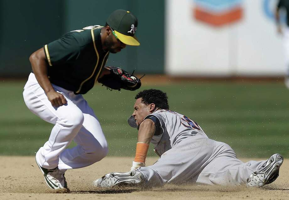 Astros outfielder Carlos Gomez, right, steals second base past the Athletics' Marcus Semien in the sixth inning Monday in the Astros' 10-9 loss that cut their AL West lead to two games. Photo: Ben Margot, STF / AP