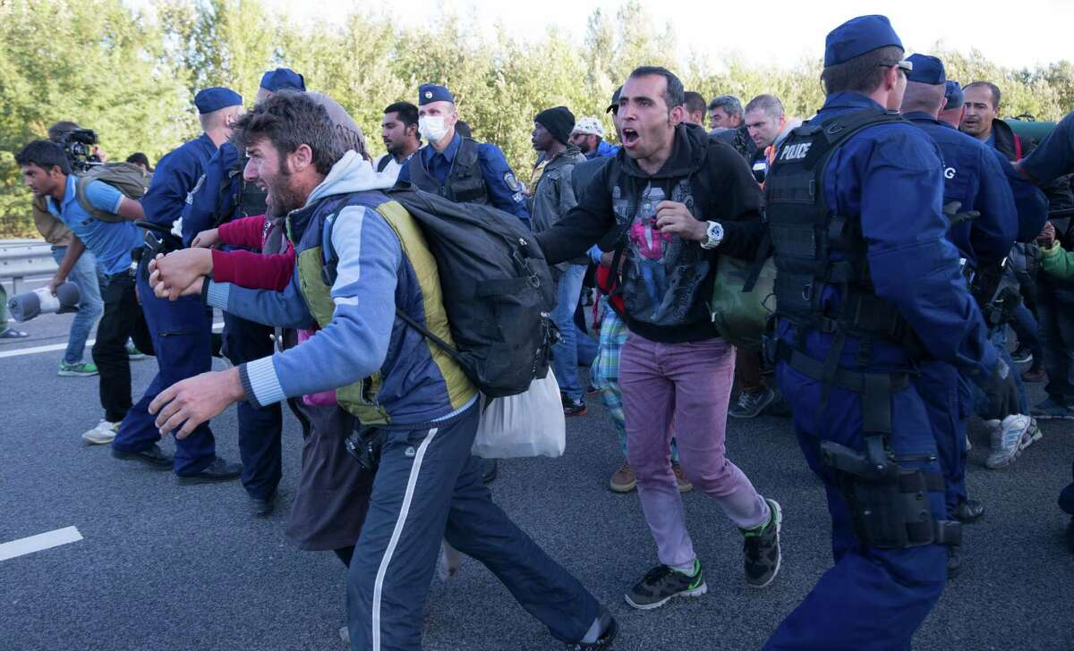 BUDAPEST, HUNGARY - SEPTEMBER 07: Police try to hold back migrants who have refused to travel to the Roszke registration centre and have ran onto the nearby motorway on September 7, 2015 in Roszke, Hungary. As the migrant crisis in Europe continues, an estimated 18000 people arrived in Germany over the weekend and thousands more are following in their wake along the Balkan route. (Photo by Matt Cardy/Getty Images) ORG XMIT: 576378589