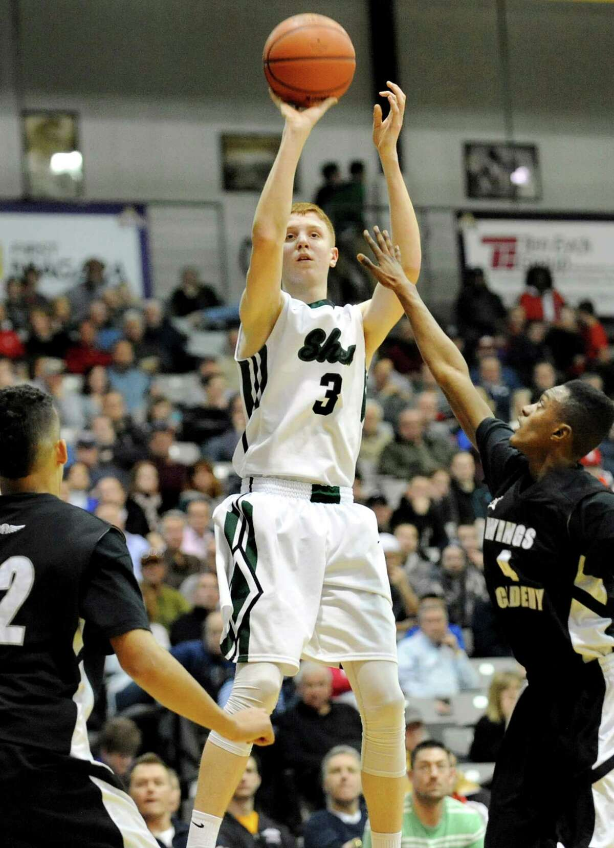 Shen's Kevin Huerter, center, hits a 3-point shot as Wings Academy's Desure Buie, right, defends in the Class AA Federation Tournament boys' semifinal on Friday, March 27, 2015, at UAlbany in Albany, N.Y. (Cindy Schultz / Times Union)