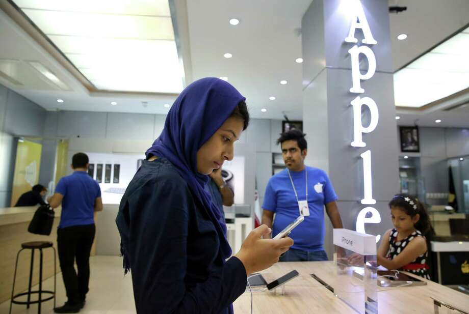 In this photo from last month, an Iranian woman tries out an iPhone in an electronics shop selling Apple products in Tehran, Iran. Under the nuclear deal, businesses are looking at Iran as a major market to enter. And those within want more access to major brands, like Apple Inc.'s iPhones, said Amir Rezvani, the sales manager of Vaghaye Gostare Fars Co., which imports Apple devices. Photo: Vahid Salemi / Associated Press / AP