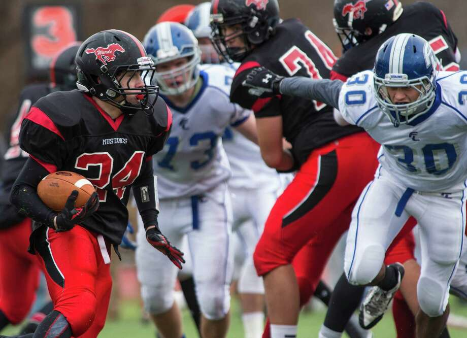 Fairfield Warde running back Bryan Azarian looks for a hole in the Fairfield Ludlowe defense during Thanksgiving day action last season. The Mustangs finished 6-5, their first winning season since the two schools split in 2004. Photo: Mark Conrad / Mark Conrad / Connecticut Post Freelance