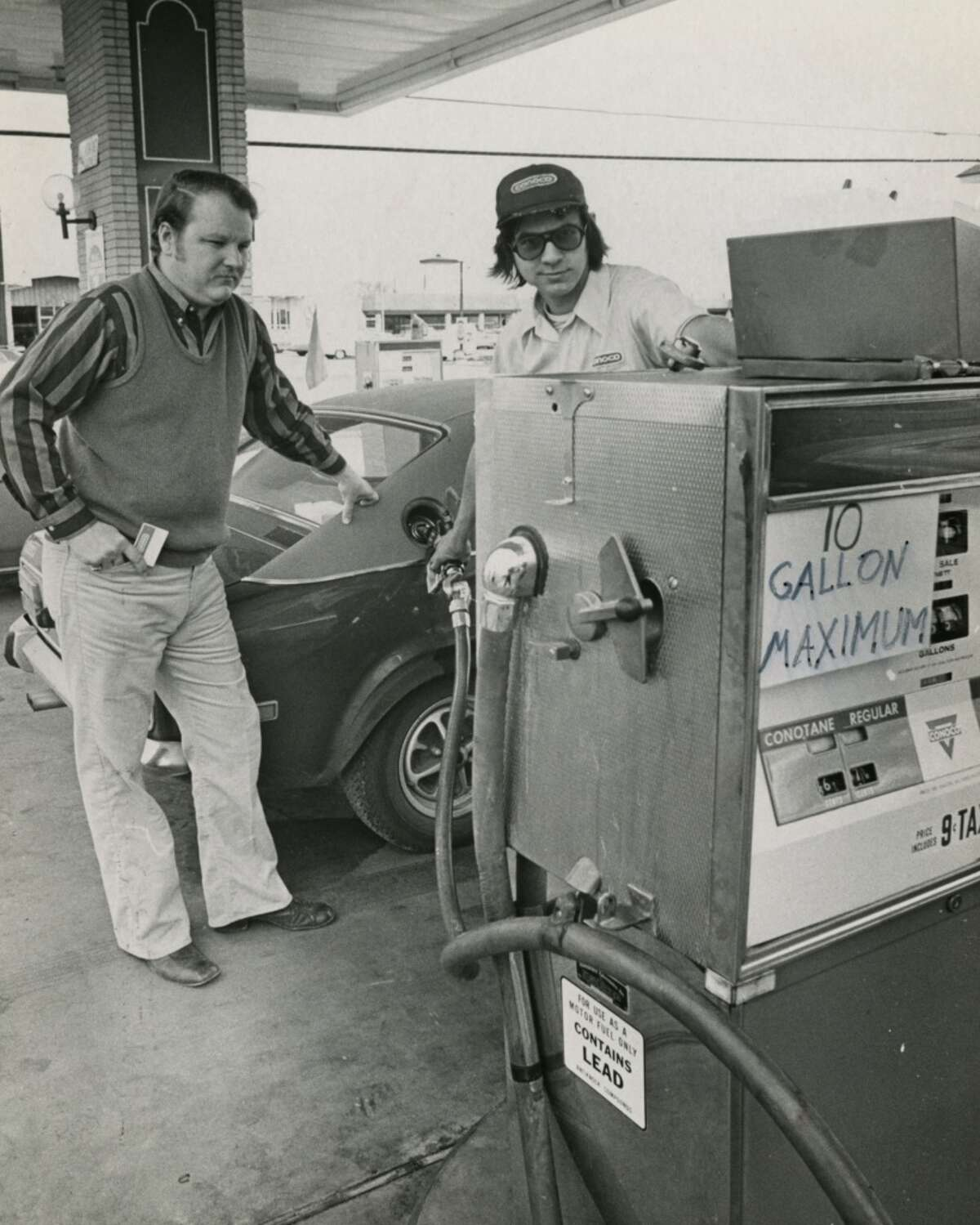 On Dec. 21, 1973, John O. Pickett (left) waits while attendant Ron West pumps gas into Pickett's car at the Westchester Conoco station on Memorial Drive at Dairy Ashford Street in Houston. The station limited sales over the holiday weekend to 10 gallons per customer while most Texas stations closed.
