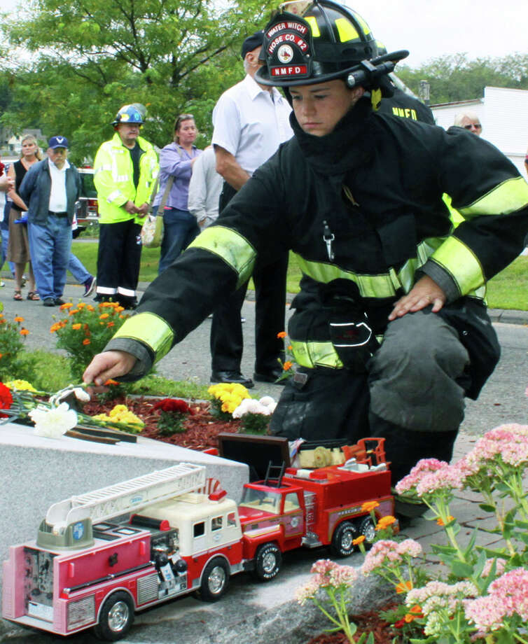Next Friday will mark the 14th anniversary of the horrific terrorist attacks on the United States, and residents throughout the Greater New Milford area will pay tribute to those who died in New York City, Washington D.C. and Pennsylvania at remembrance services. Above, Water Witch Hose Co. No. 2 firefighter Maureen Hickey places a flower on the 9/11 memorial at Patriot's Way during last year's annual 9/11 service in New Milford. Photo: Walter Kidd / The News-Times Freelance