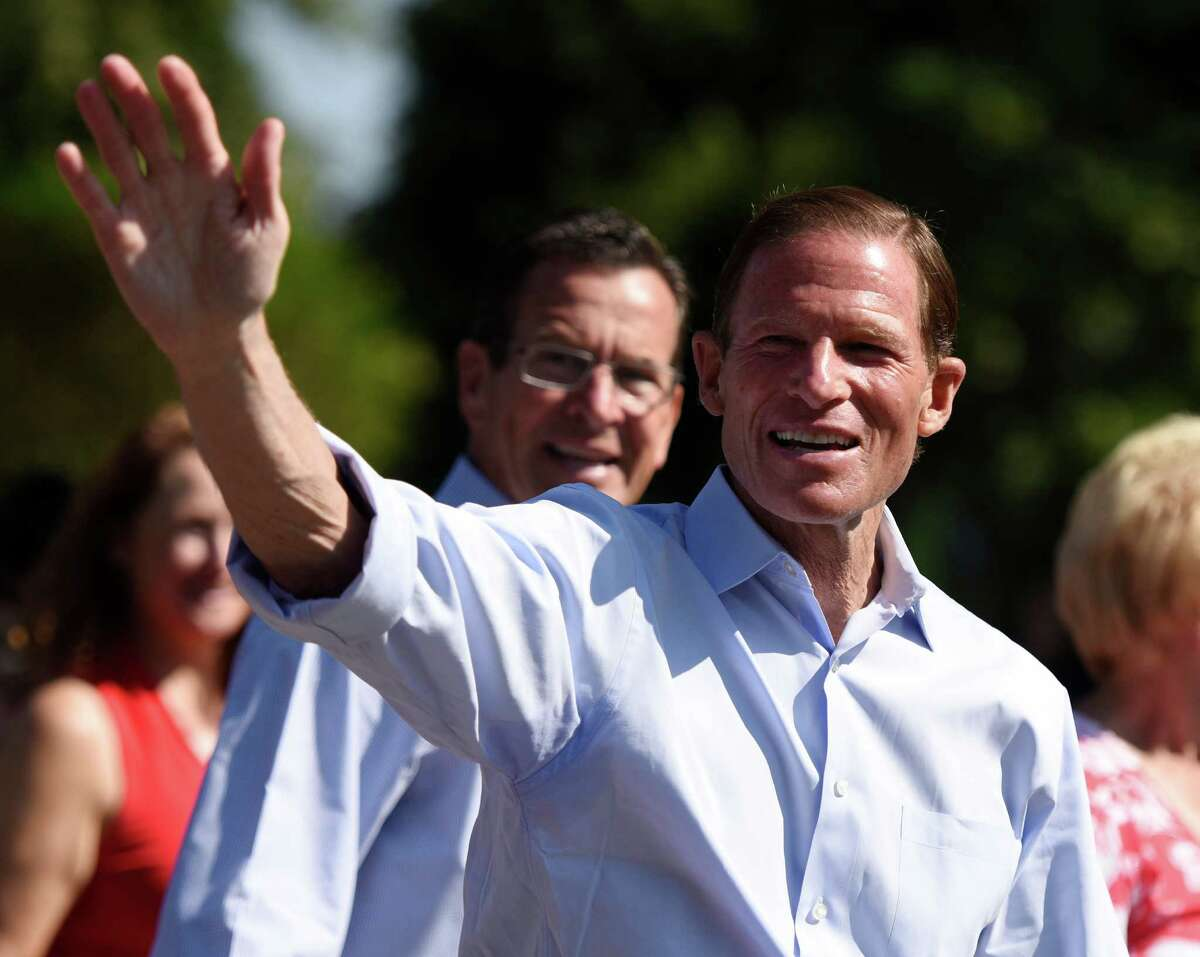 U.S. Sen. Richard Blumenthal waves to the crowd while marching in the 54th annual Newtown Labor Day Parade in Newtown on Monday.