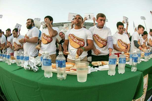 Bridgewater employees participating in a hot dog eating contest at the firm's annual summer picnic.