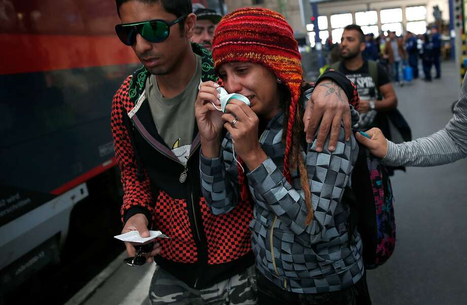 A Syrian woman cries after being caught between refugees trying to board a train for Vienna at Budapest's Keleti station. Photo: Win McNamee, Getty Images