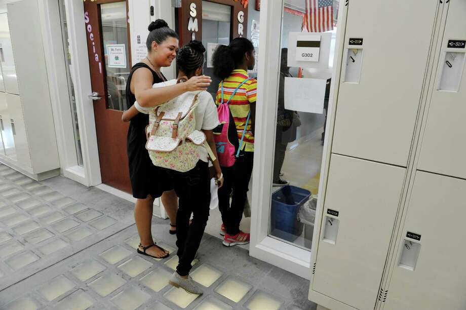 English Language Arts teacher, Bridget Smith, welcomes a student during the first day of school for students at West Hill Middle School on Tuesday, Sept. 8, 2015, in Albany, N.Y.  (Paul Buckowski / Times Union) Photo: PAUL BUCKOWSKI / 00033248A