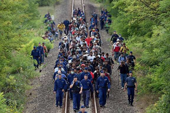 TOPSHOTS Refugees of different countries accompanied by police officers walk on the railway tracks near Szeged town as they broke out from the migrant collection point near Roszke village of the Hungarian-Serbian border on September 8, 2015. Hungary's border with Serbia has become a major crossing point into the European Union, with more than 160,000 entering Hungary so far this year including 2,706 on September 7, 2015 alone, police said.