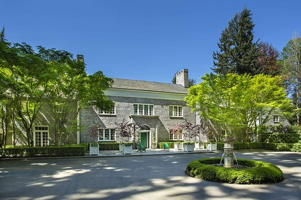 The property covers almost three acres and has views of Puget Sound and the Olympics. It includes a large courtyard with a fountain in the center.