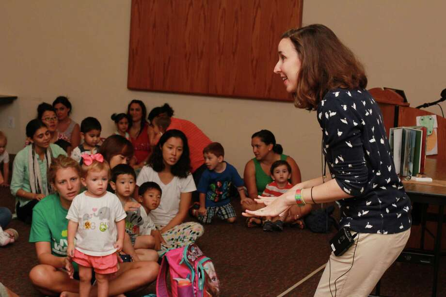 "Meagan Hopkins, with the Cinco Ranch Library gets ""Toddler Time"" started with a throng of younsters at the Cinco Ranch Branch Library, which has added more times for the event to meet growing demand. If approved by voters, a Fort Bend County bond package would include fundsto build another library in the area. Photo: Jimmy Loyd / freelance"