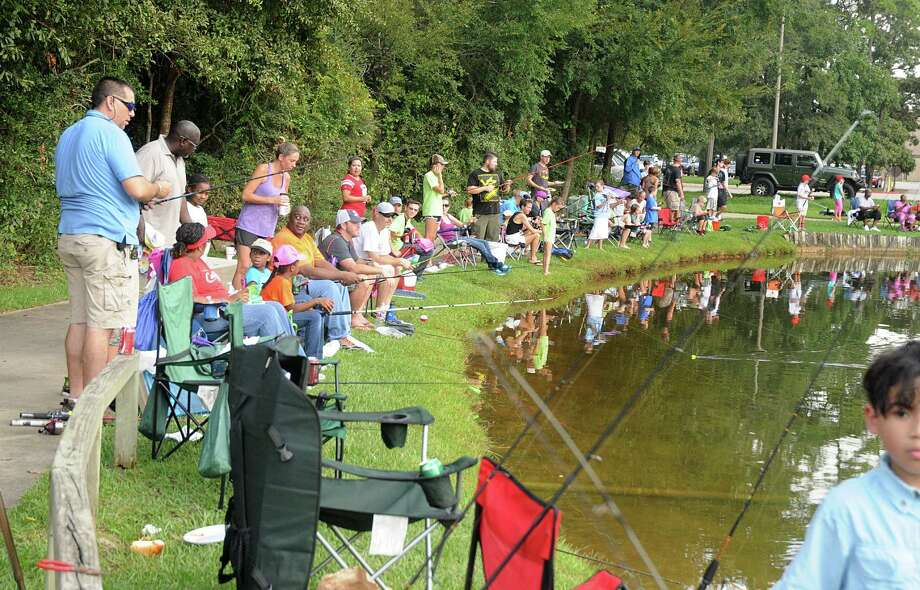 "Children and their parents line the banks as they try to catch the ""big one"" during The Woodlands Kiwanis Club's 32nd Annual Kids Fishing Tournament at Creekwood Park pond, 3383 S. Panther Creek. Toddlers to 16 year olds, and their parents, were invited to participate in the fishing tournament. Photograph by David Hopper. Photo: David Hopper, For The Chronicle / freelance"