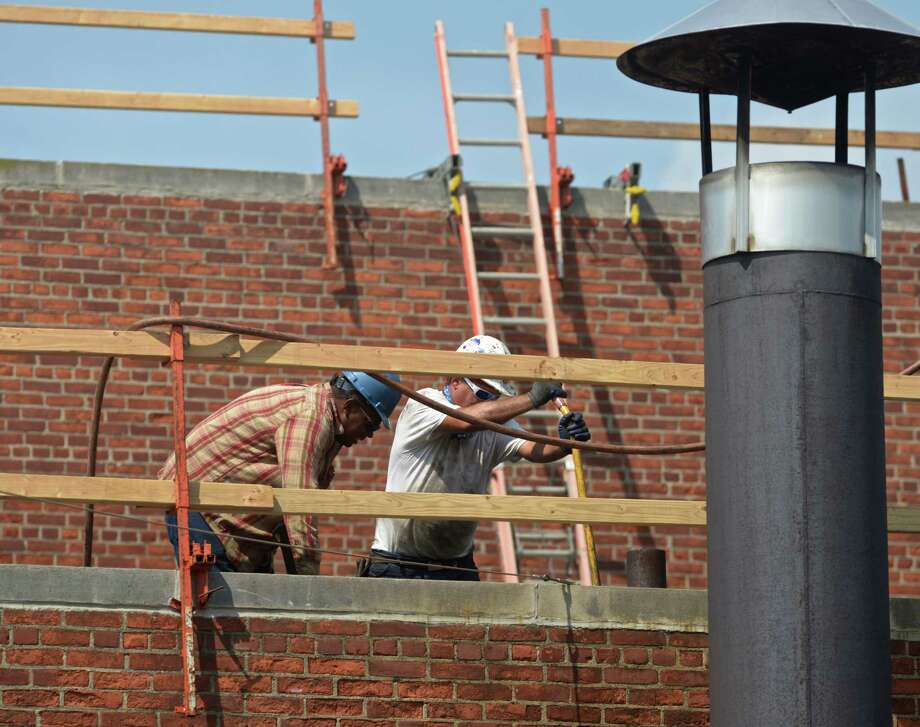 Workers replace the roof on the Danbury War Memorial Tuesday afternoon. September 8, 2015, in Danbury, Conn. Grant money is being used to upgrade the 1951 War Memorial building. Photo: H John Voorhees III / Hearst Connecticut Media / The News-Times