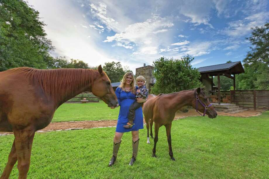 Realtor Lauren Taylor holds her 3-year-old son Grady as they wander among the horses on her property in Spring Branch. Taylor lives in the house her grandparents built in the Bunker Hill area. Photo: Courtesy