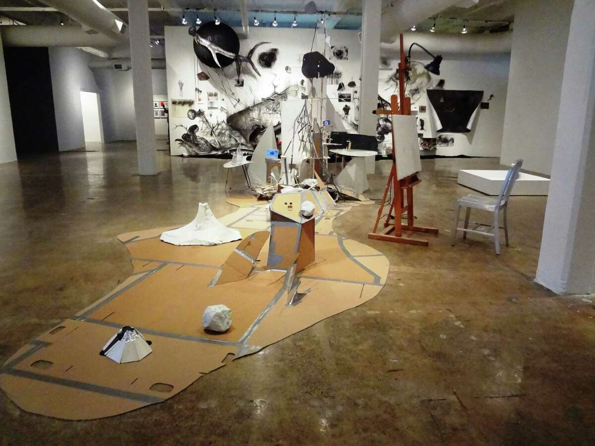 """Patte Loper's installation """"After Lebbeus: A Model for Drawing"""" is in the foreground, while Arturs Virtmanis' """"A Sorry Theory of Everything"""" is on the back wall."""