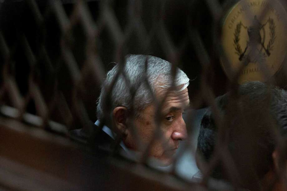 Guatemala's former president Otto Perez Molina, photographed through a window, sits in court in Guatemala City on Tuesday for a third hearing on corruption allegations that led him to resign last week.  Photo: Esteban Felix, STF / AP