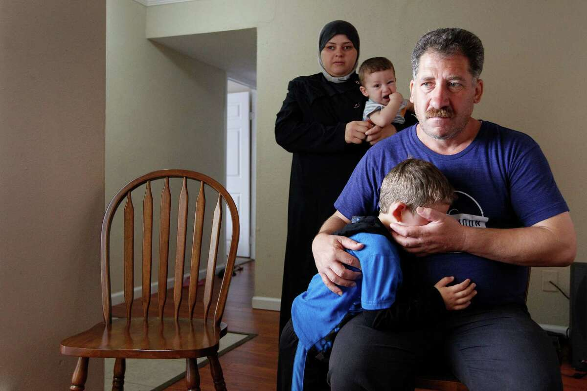 Emad and Manal Alhalabeya, and their family of eight, are Syrian refugees who recently arrived in Houston. They're seen here during an interview at their west Houston apartment in September. Emad Alhalabeya (foreground) comforts his son, Noor, as his wife, Manal holds their son, Sultan.