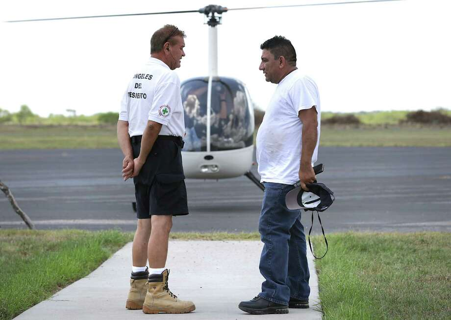 Rafael Hernandez, left, of Angels of the Desert, talks with a disappointed Rolando Arriaza, a Guatemalan immigrant living in Philadelphia, on Tuesday, after flying in a helicopter over private ranches near Falfurrias while searching for his missing brother, Hugo. Photo: Bob Owen /San Antonio Express-News / ©2015 San Antonio Express-News